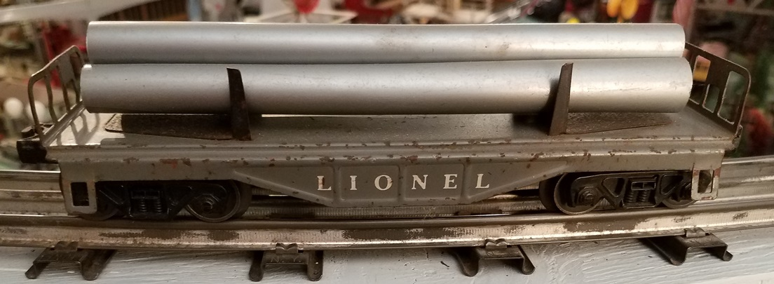 Lionel Postwar 6121 gray flatcar with pipes