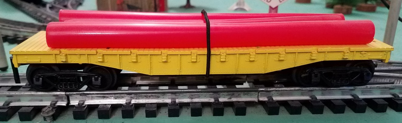 Unlettered yellow flatcar with red pipes